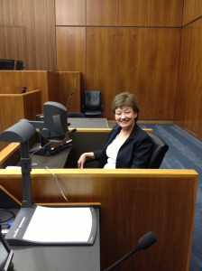 Colleen, our courtroom deputy supervisor, sits in the witness box to illustrate to the prospective panel how the equipment works.  The prospective jury panel members gather around her as she illustrates and I yap.