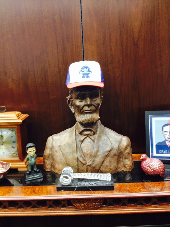"In my chambers near my conference table sits my bust of Lincoln (given to me by Chris Cook, a really good lawyer and even better artist) now wearing my new Pabst Blue Ribbon hat given to me by the bad Matt. Don't be distracted by the ""dear leader"" bobblehead. The law clerks pray to that one."